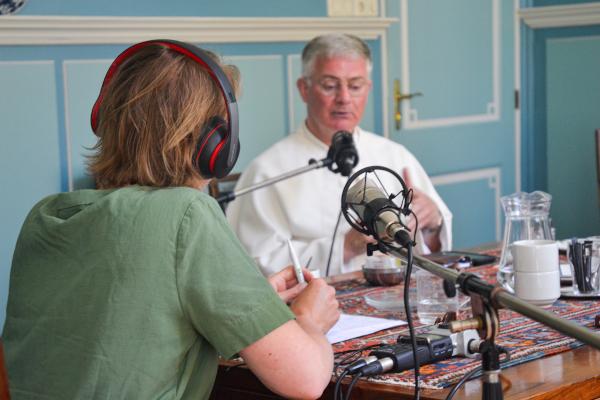 Een van de norbertijnen bij de opname van een podcast